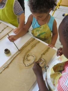 Les enfants peignent les colombins couleur or