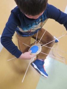 Enfant tressant une armature en rotin
