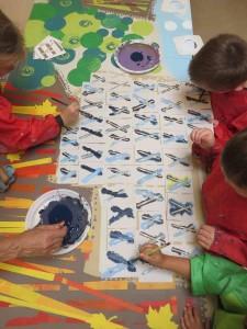 Groupe d'enfants qui peignent avec des pochoirs