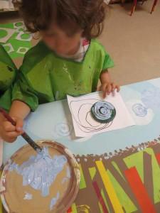 Enfant qui enduit son tampon de peinture