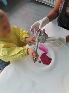 Petite fille qui peint aidée de sa maman