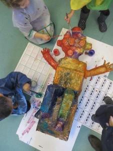 Enfants qui peignent leur sculpture géante
