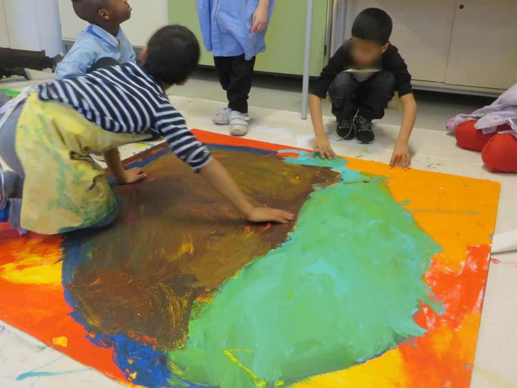 Enfants qui peignent au sol