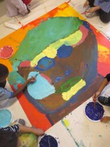 Les enfants peignent un grand portrait