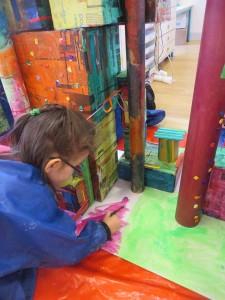Petite fille qui peint le sol de sa maquette
