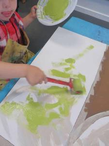 Enfant qui peint avec un rouleau en mousse