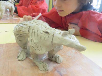 Enfant qui réalise une sculpture en argile