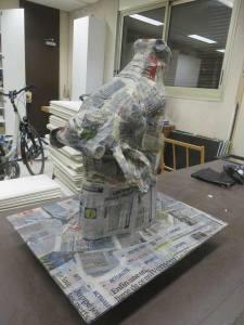 La sculpture est recouverte de papier journal enduit de colle à tapisser