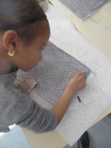 Petite fille qui colorie sa feuille en gris