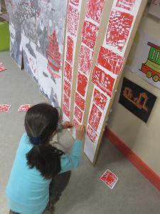Une petite fille colle les hanku sur la fresque