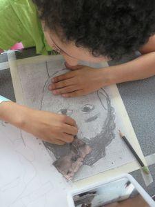 Aurélien dessine son portrait face à un miroir