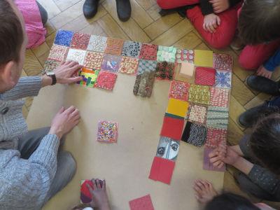 L'instituteur aide les enfants dans leur recherche de composition
