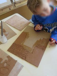 Enfant qui dessine avec de l'argile