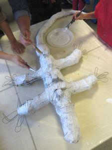 Les enfants peingnent leur lézard en papier mâché