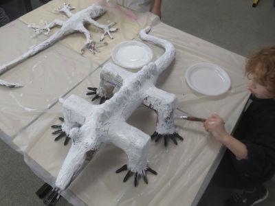 Un enfant peint sa sculpture