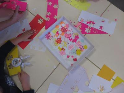 Les enfants découpent des vignettes pour décorer leurs lézards