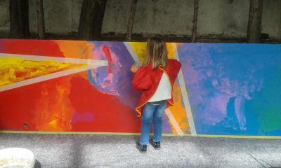 Filette qui peint une fresque dans la cour