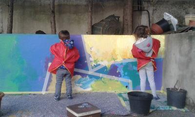 Les enfants s'appliquent à peindre une fresque