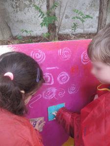 Les enfants décorent le mur avec des tampons