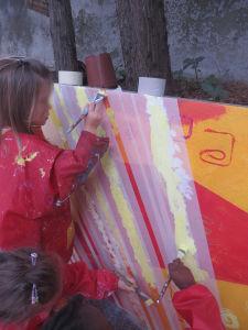 Fillette qui peint sur le mur de son école