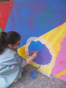 Enfant qui peint un rond à l'aide d'un pochoir