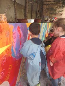 Les enfants réalisent les finitions sur leur fresque
