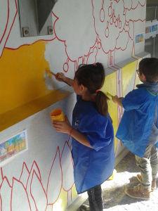 Filette qui peint le mur de son école