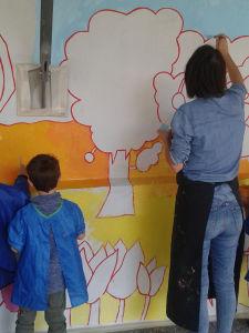 Chacun peint une partie du mur à sa hauteur