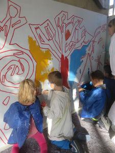 Les enfants découvrent le plaisir de peindre directement sur le mur
