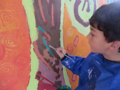 Un enfant réalise les derniers détails de la fresque