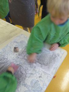 Les enfants frottent une mine graphite sur du papier machine