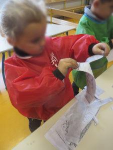 La fillette déchire les feuilles de papier