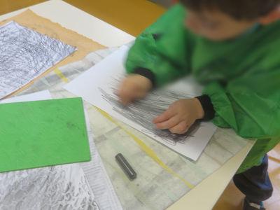 Un enfant frotte de la mine de crayon à papier sur une feuille