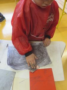 L'enfant frotte sa feuille avec du papier buvard