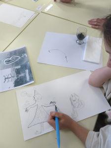 Enfant dessinant à la plume