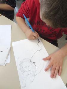 Enfant qui dessine à l'école