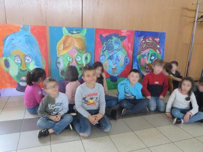 Les enfants posent devant leurs peintures