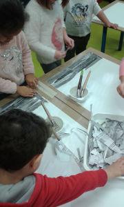 Les enfants fabriquent un ciel avec des bandes de papier gris