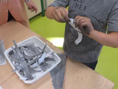 Déchirer le papier gris en bandelettes
