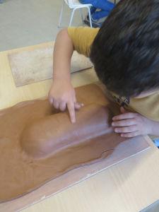 Modelage d'un masque en argile rouge