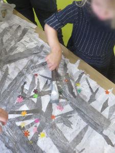 Une fillette colle les bandes de papier