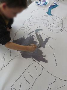 Un enfant peint l'éléphant en gris