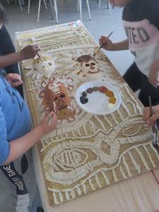Les enfants collaborent pour créer une oeuvre collective