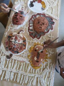 Les enfants peignent leur masque en argile