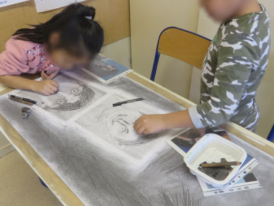 Les enfants réalisent un grand dessin collectif