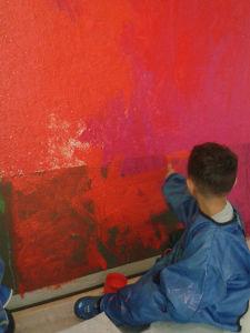 Enfant de PS/MS en tran de peindre le mur