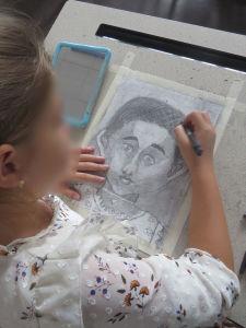 Une fillette dessine sont autoportrait