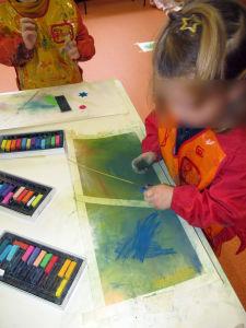 Fillette qui joue avec les pastels