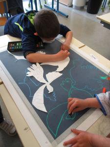 Un enfant s'applique à dessiner un oiseau