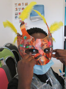 Le masque de Layann avec ses plumles jaunes